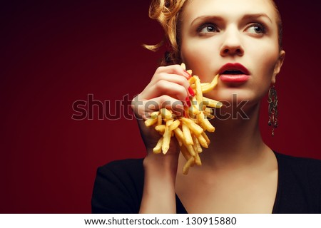 Unhealthy eating. Junk food concept. Portrait of fashionable young woman holding (eating) fried potato (fries, chips) in her hand and posing over red background. Close up. Copy-space. Studio shot - stock photo
