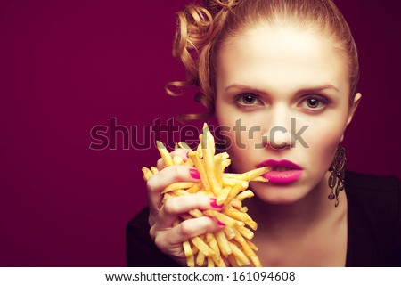 Unhealthy eating. Junk food concept. Portrait of fashionable young woman holding (eating) fried potato (fries, chips) in her hand and posing over purple background. Close up. Copy-space. Studio shot
