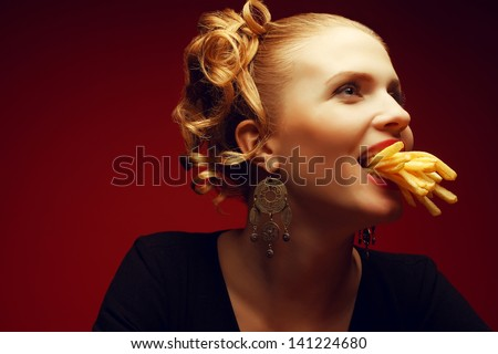 Unhealthy eating. Junk food concept. Profile portrait of fashionable young woman holding (eating) fried potato (fries, chips) in mouth and posing over red background. Close up. Copy-space. Studio shot - stock photo
