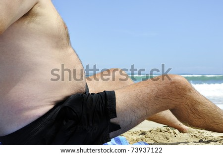 Unhealthy fat man sitting on the beach on a sunny day - stock photo