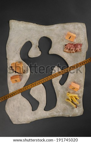 Unhealthy food victim. Crime scene, a silhouette of a man made out of baking dough, next to several evidences about the cause of death. Cause and effect of unhealthy eating. Easily customizable.   - stock photo