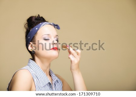 Unhealthy junk food concept. Happy lovely girl retro style eating sweets food cookie cake copyspace brown background - stock photo
