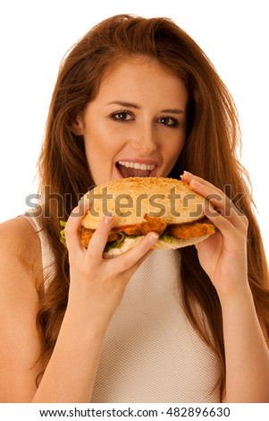 Unhealthy meal - happy young woman eats hamburger isolated over white