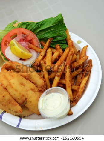 unhealthy meal with fried fish sandwich and fries - stock photo