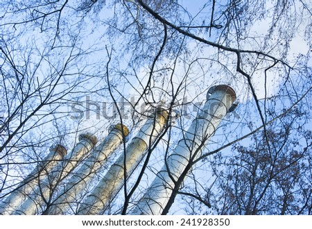 unhealthy smoke from the chimney against the blue sky - stock photo