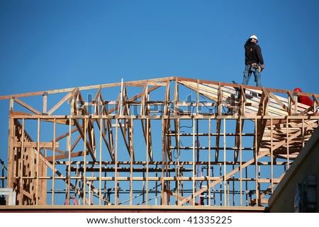 unidentifiable construction workers work on framing a building - stock photo