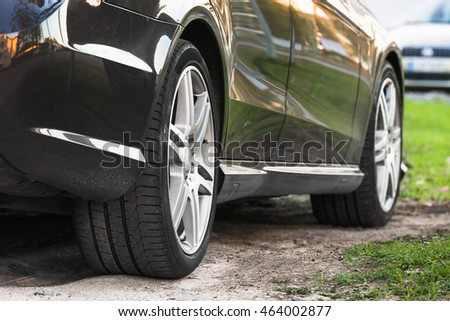 Unidentifiable shining luxury car fragment with wheels on grass