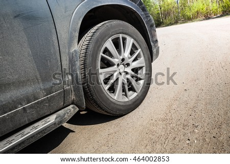Unidentifiable SUV car fragment. Wheel with light alloy disc on country road in summer, close up photo