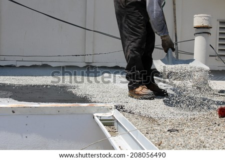 """Unidentifiable workers use """"Hot Tar"""" aka """"Hot Mop"""" to lay down Molten Tar, Asphalt Sheets and Pea Gravel on a Flat roof on a Hot Summer day in Southern California. Roofs are important on houses - stock photo"""