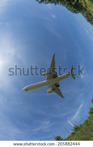 Unidentified aircraft flies above taken with a fisheye lens. - stock photo