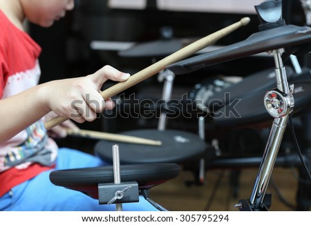 Unidentified Asian boy play electronic drum in music room - stock photo
