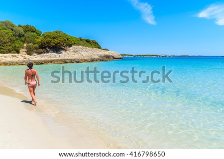 Unidentified attractive young woman in swimsuit walking along beautiful Petit Sperone beach on Corsica island, France - stock photo