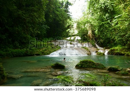 Unidentified female tourist swimming in the waterfalls at Reach Falls which are one of the most popular tourist destinations and attractions in Portland parish, Jamaica on December 30, 2013.  - stock photo