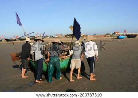 Unidentified fishermen pulling a fishing boat on the beach after voyage in early morning on Aug 1, 2014 at Hai ly, Nam dinh, Vietnam. This location is very famous for salt production and fisheries.