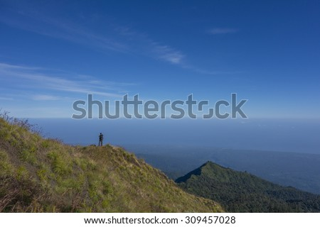 Unidentified hiker takes a photo at 2,500m above sea level at Plawangan Senaru on his way to climb Rinjani Mountain in Lombok. - stock photo