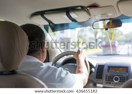 Unidentified male driver driving a modern car. Image taken from the back seat. Focus point on the man's shoulder.