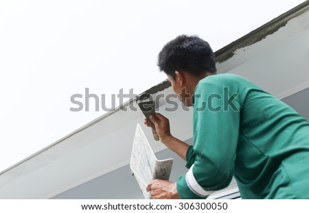 Unidentified man plastering  concrete to shape the edge of the wall on house construction - stock photo