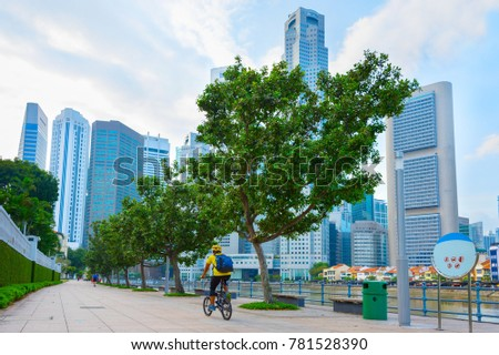 Unidentified man riding bicycle on Singapore river embankment