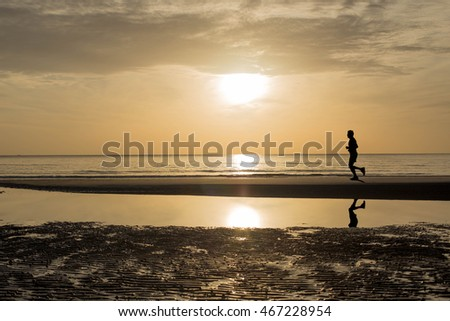 Unidentified man running at sunset - sunrise on the beach in silhouette