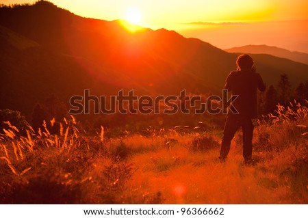 Unidentified man stand and take photo a beautiful view of grass field and Himalayan mountains in sunrise time at the top of Poonhill peak, Nepal - stock photo