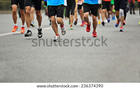 Unidentified marathon athletes legs running on  city road  - stock photo