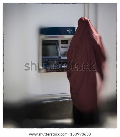 Unidentified muslim woman seen from behind by cashpoint drawing cash.