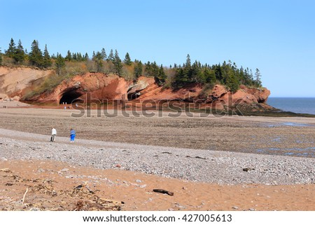 Unidentified people enjoying the rocky beach and caves at low tide in  St. Martins, New Brunswick, in the Maritime Provinces of Canada