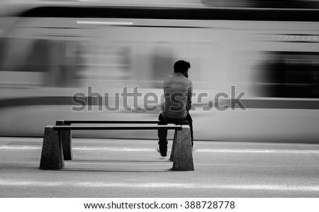 Unidentified people waiting Train Station Lifestyle Concept view in black and white. .Image has blurry or noise and soft focus when view at full resolution.(Shallow DOF, slight motion blur) - stock photo