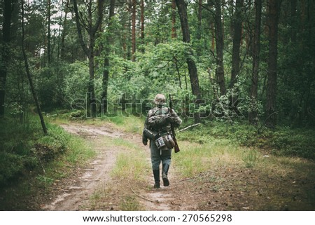 Unidentified re-enactor dressed as German soldier during march through summer forest - stock photo