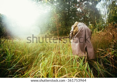 Unidentified re-enactor dressed as Soviet russian soldier running through woods in fog - stock photo