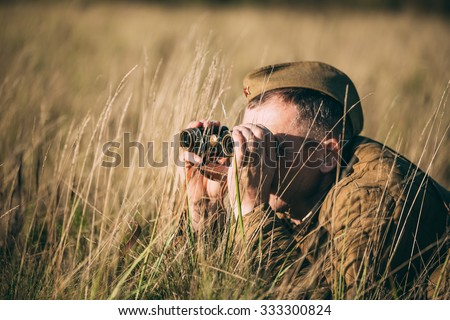 Unidentified re-enactor dressed as Soviet soldier looks at an old army binoculars. - stock photo
