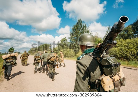 Unidentified re-enactors dressed as German soldiers during march through summer forest