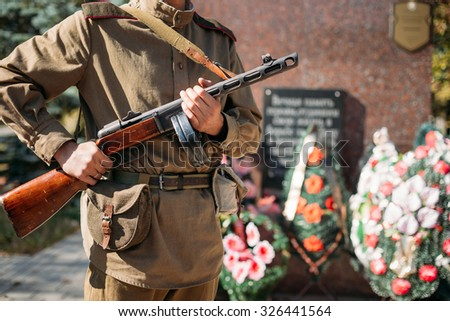 Unidentified reconstructor dressed as Soviet soldier with submachine gun, standing on background of mass grave of Soviet soldiers who died during battles for liberation of Belarus during World War II - stock photo