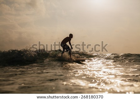 unidentified surfing man silhouette in ocean waves at sunrise - stock photo