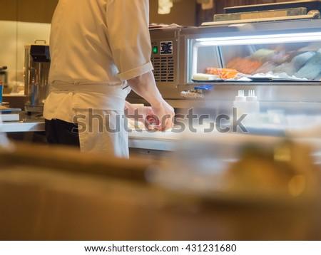 unidentified sushi chef preparing sushi - stock photo