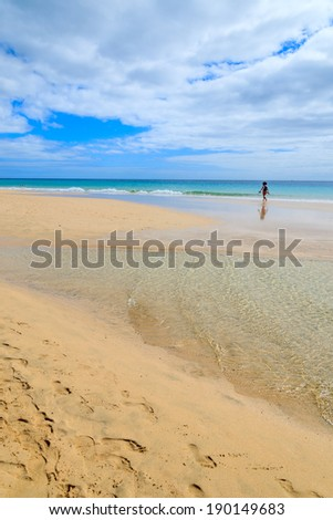 Unidentified tourist walks along idyllic lagoon beach on Jandia peninsula, Morro Jable, Fuerteventura, Canary Islands, Spain