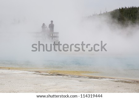 Unidentified tourists standing in the middle of a hot sulfur spring in Yellowstone National Park, Wyoming, USA - stock photo