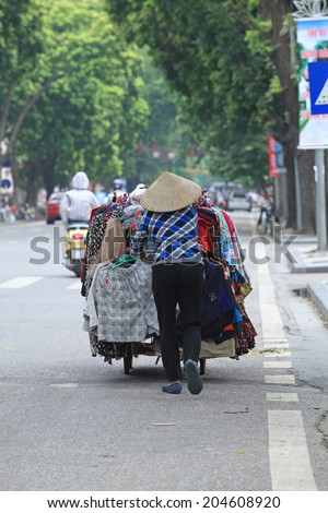 Unidentified Vietnamese vendor pushing her mobile stall of clothes on a Hanoi street.  - stock photo