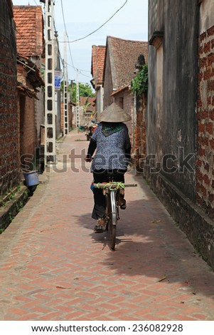 Unidentified Vietnamese woman cycling on a country road of old Duong Lam village in Hanoi, Vietnam. - stock photo