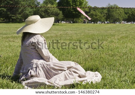 Unidentified woman actor in sun hat and period dress sits waiting by roped-off battlefield during reenactment of battle in the American Civil War (1861-1865) - stock photo