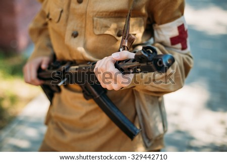 Unidentified woman reconstructor dressed as a Soviet military nurse with a submachine gun in hand. Close up on hands - stock photo