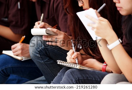 unidentified young asian female student school girls wearing jeans sitting on the floor outdoor taking note at site visit on small paper notebook with pen and pencil  - stock photo