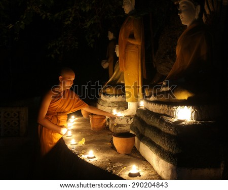 Unidentified young Buddhist novice lights a candle at the temple on November 17, 2012 in Chiang Mai province, Thailand