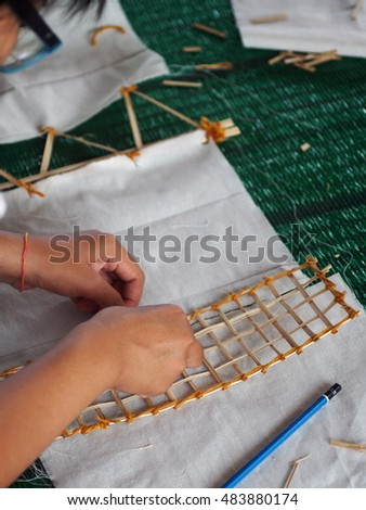 unidentified young generation asian student on practice working try apply vintage retro style material and technique on making modern decorative element cloth flag create for THAI ritual ceremony