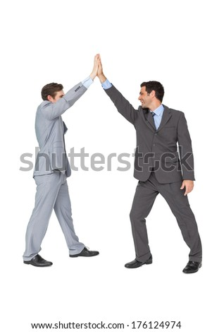 Unified business team high fiving each other on white background - stock photo