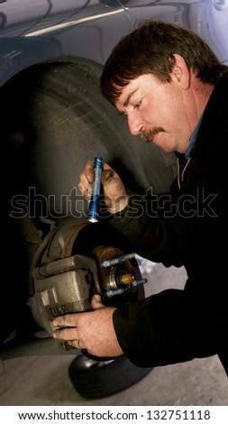 Uniformed Auto Technician Uses Mini Light to check brakes on a Car - stock photo