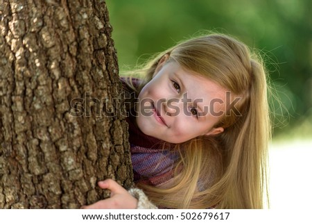 Unimaginably beautiful blond girl playing in the park hiding behind a tree.