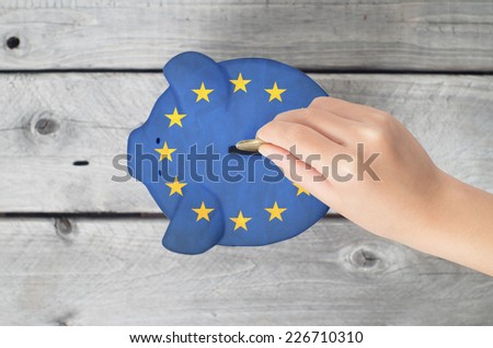 Union European saving concept with little hand dropping a coing into piggy bank overlaid with EU flag - stock photo