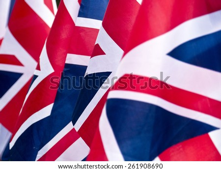 Union Jack Flags background; rippling red white and blue silken flags; differential focus   - stock photo