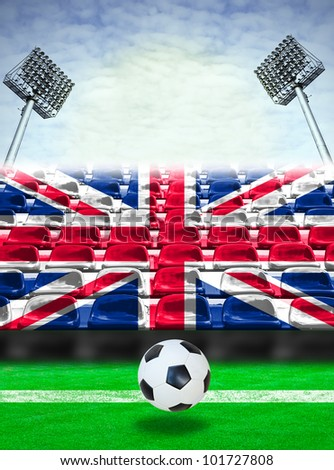Union Jack of England flag pattern on seats at outdoor sport stadium with soccer ball. - stock photo